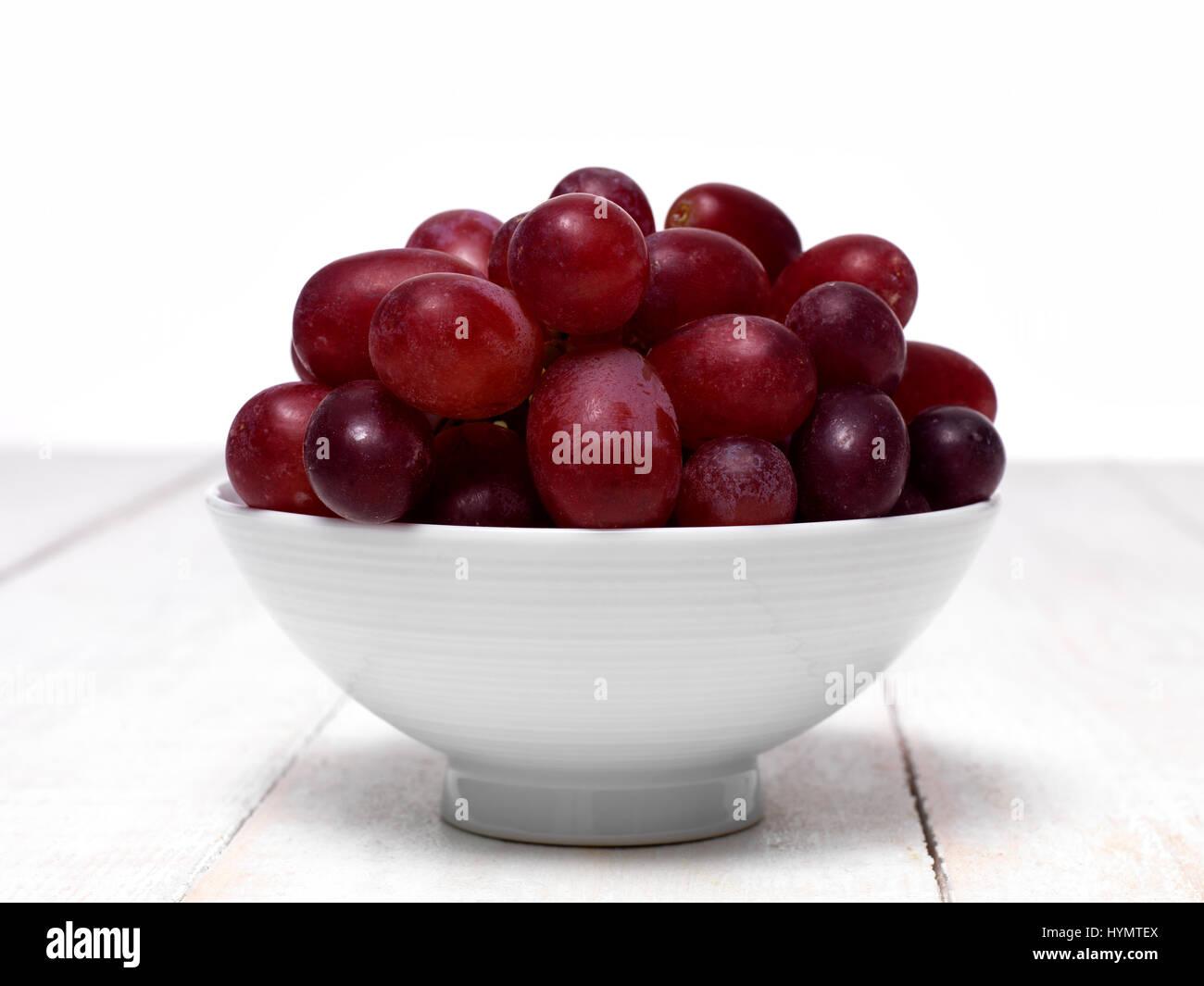 Las uvas rojas en un tazón pequeño Foto de stock