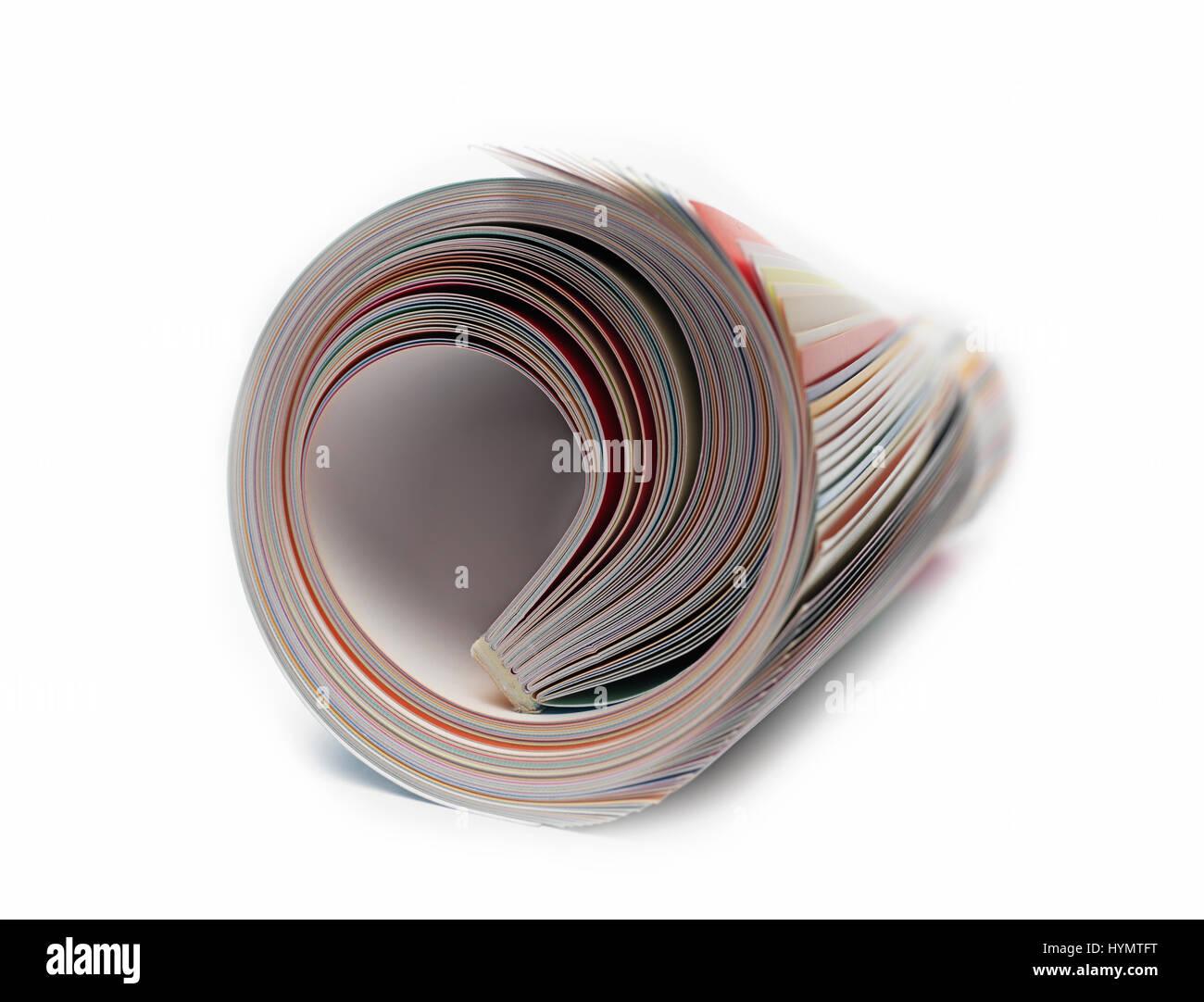 Revista enrollada sobre blanco Foto de stock