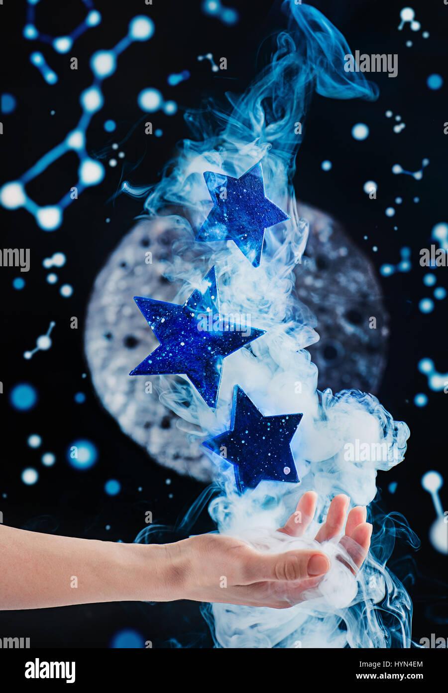 Alcanzar las estrellas: una mano con Falling Stars y humo Imagen De Stock