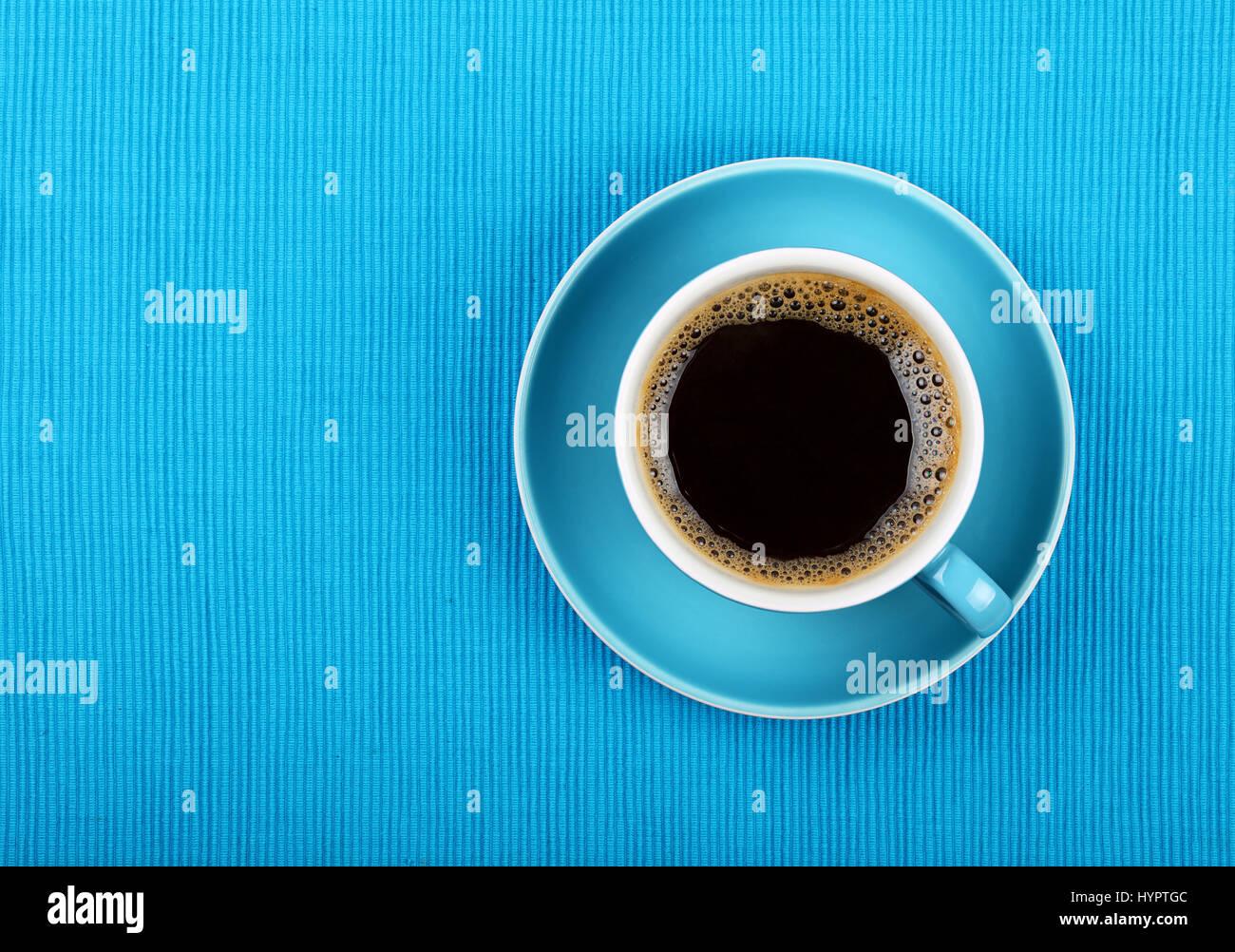 Taza llena de negro americano o café instantáneo en un platito sobre un mantel azul, cerrar, niveles elevados Imagen De Stock
