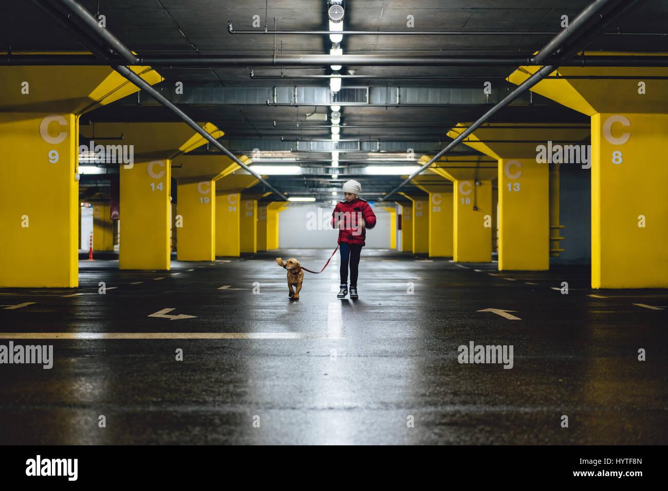 Vestida de chaqueta roja y sombrero blanco caminando en el garaje público con un pequeño perro amarillo Imagen De Stock