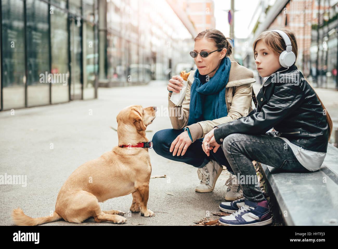 Madre comer sándwich y mirar un perro mientras hija escuchando música en la calle Imagen De Stock