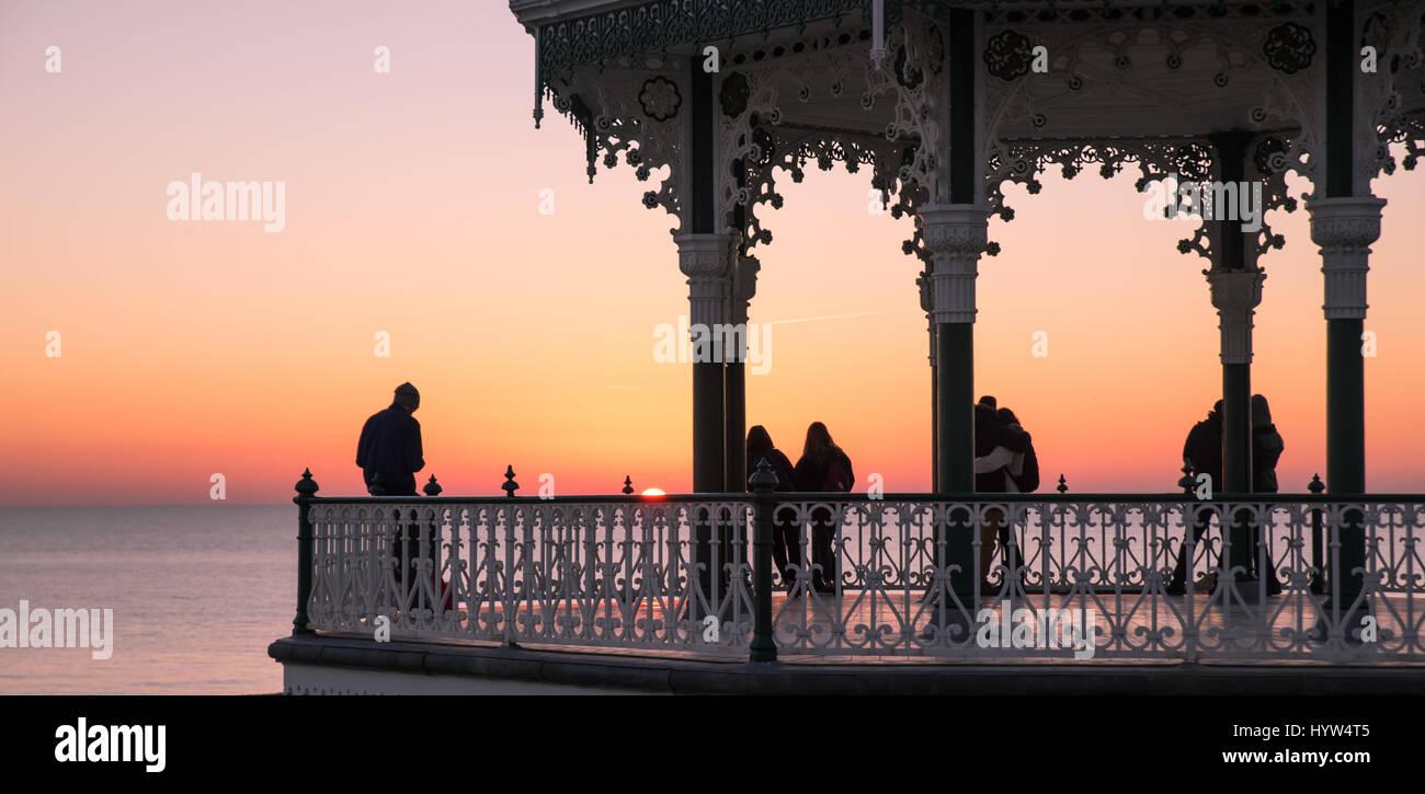 El 1 de diciembre, 2016, Brighton, Reino Unido. La gente watchiong el atardecer desde Brighton Bandstand Imagen De Stock