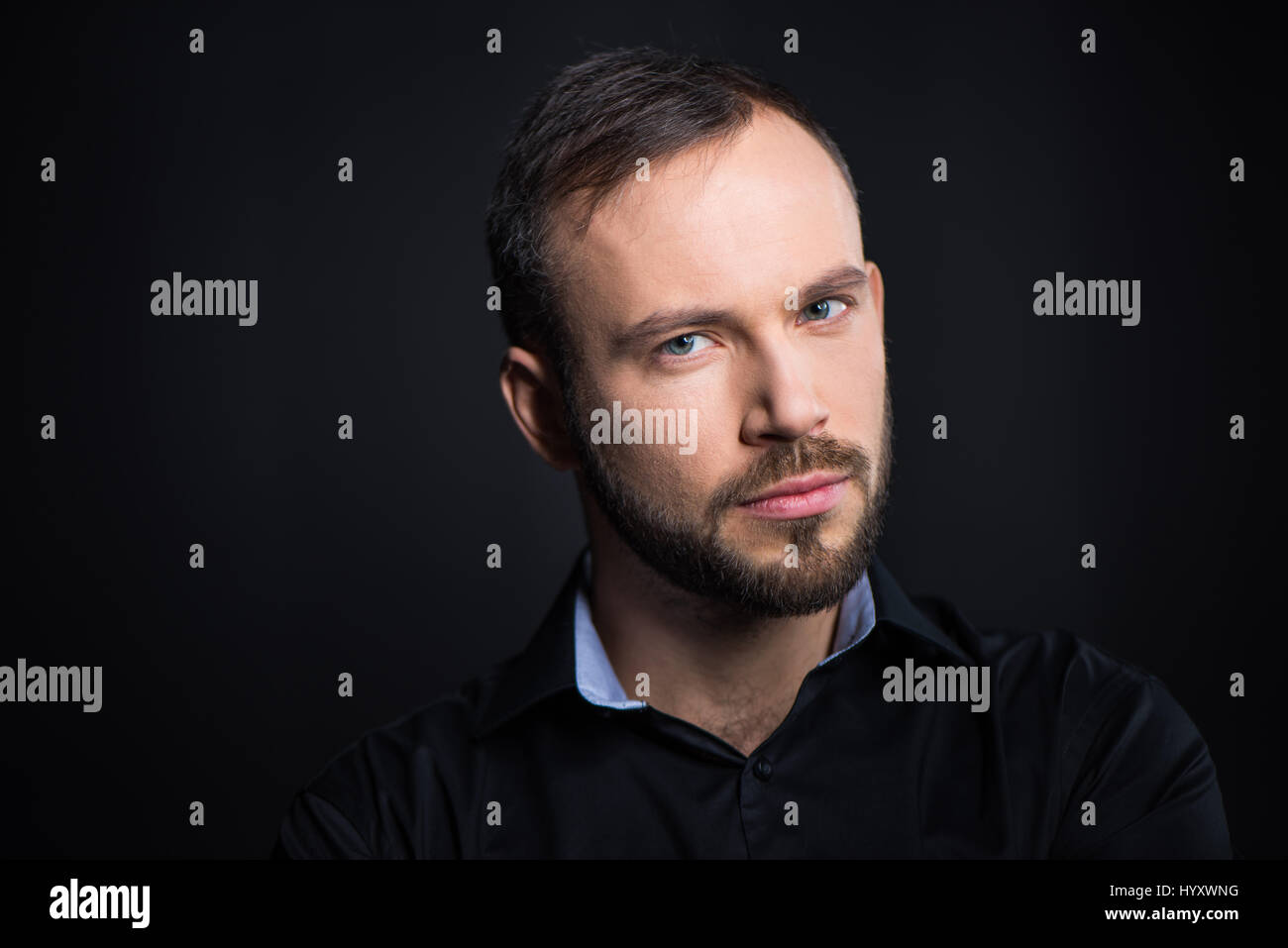 Retrato de apuesto hombre barbado mirando a la cámara sobre negro Imagen De Stock