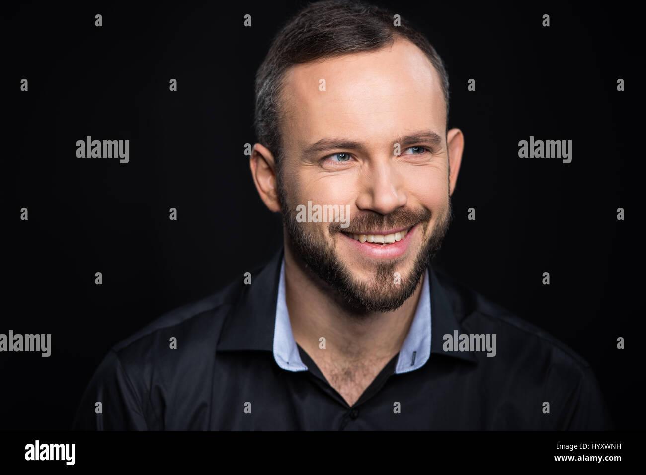 Retrato de apuesto hombre barbado sonriendo y mirando a otro lado Imagen De Stock