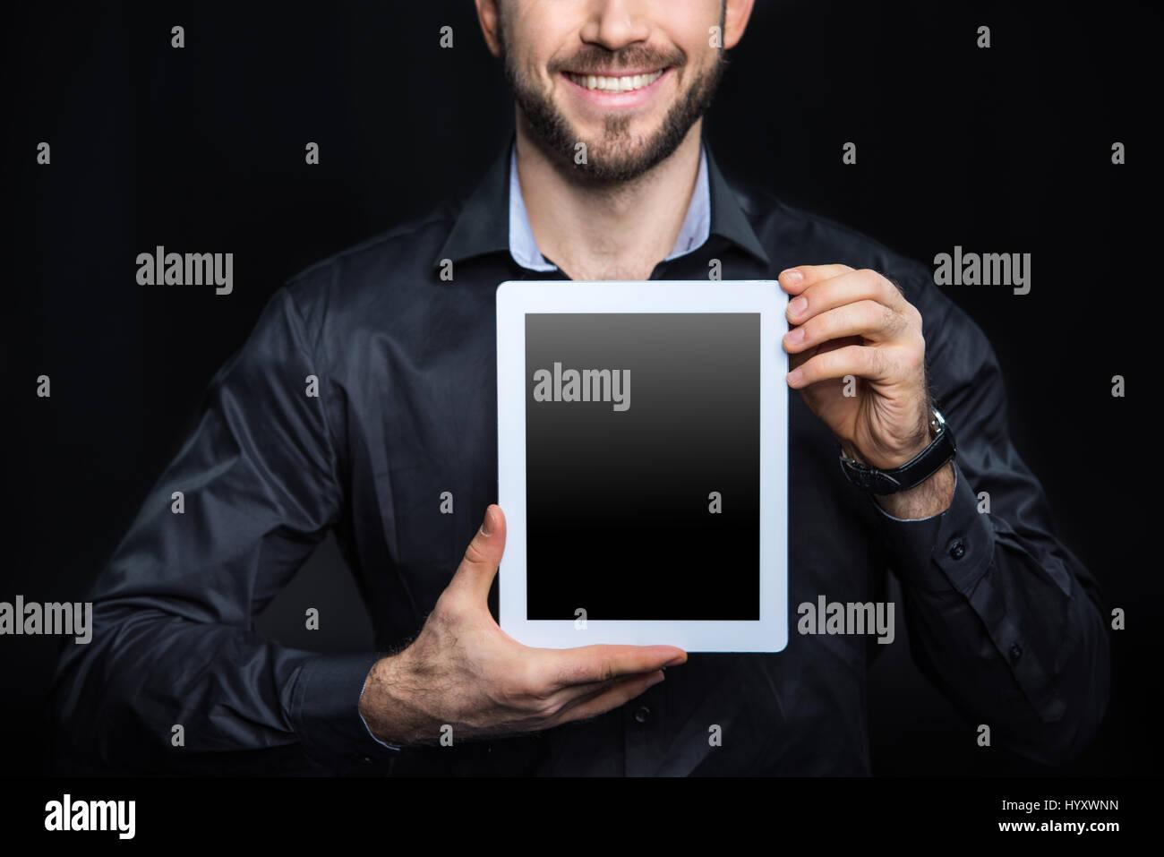 Vista parcial del hombre sonriente mostrando tableta digital Imagen De Stock