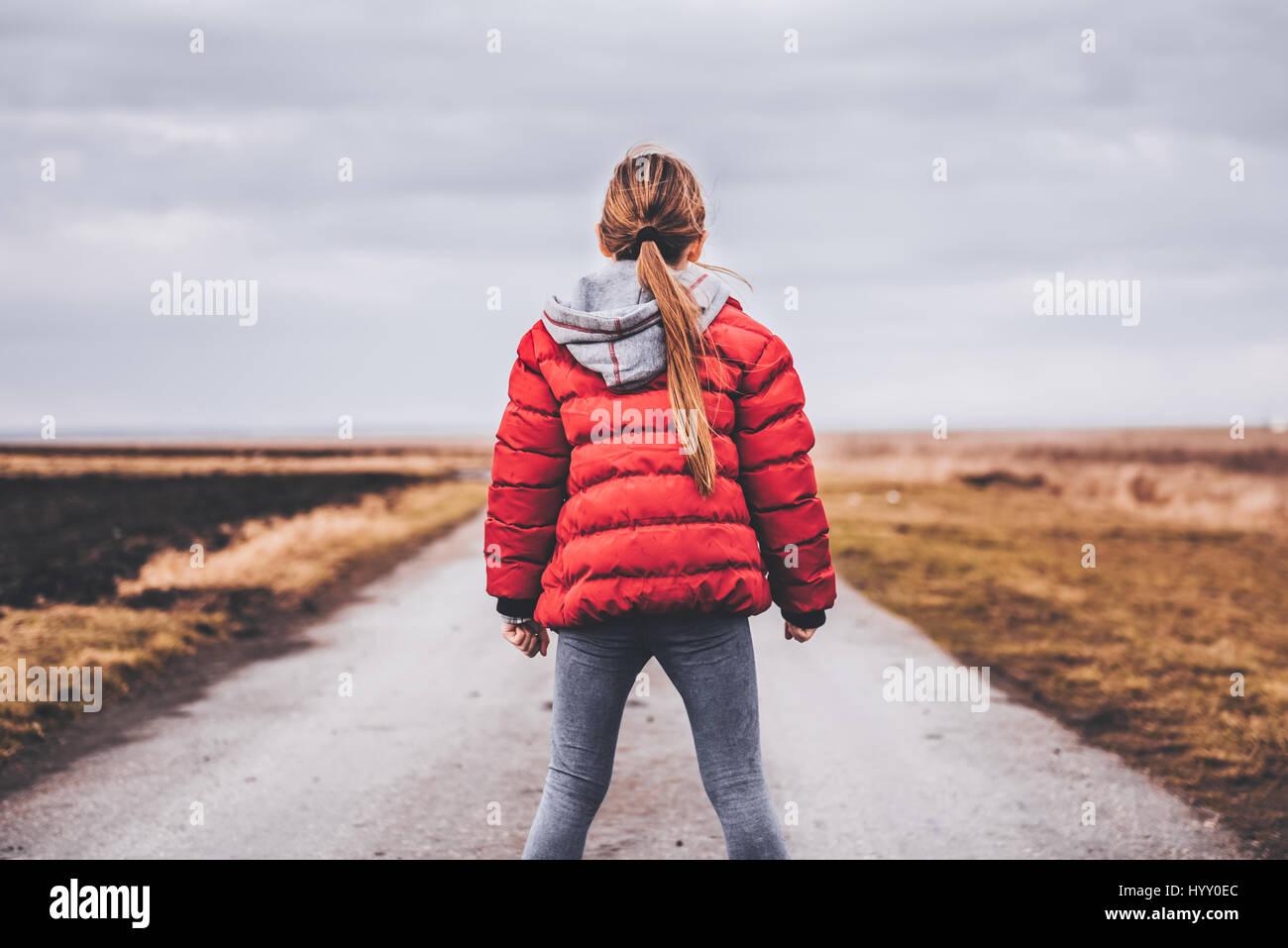 Vestida de chaqueta roja de pie solo en la carretera y mirando a distancia Imagen De Stock