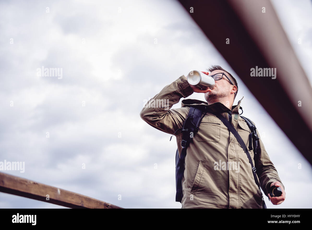 Caminante descansando sobre la valla de madera y agua potable Imagen De Stock