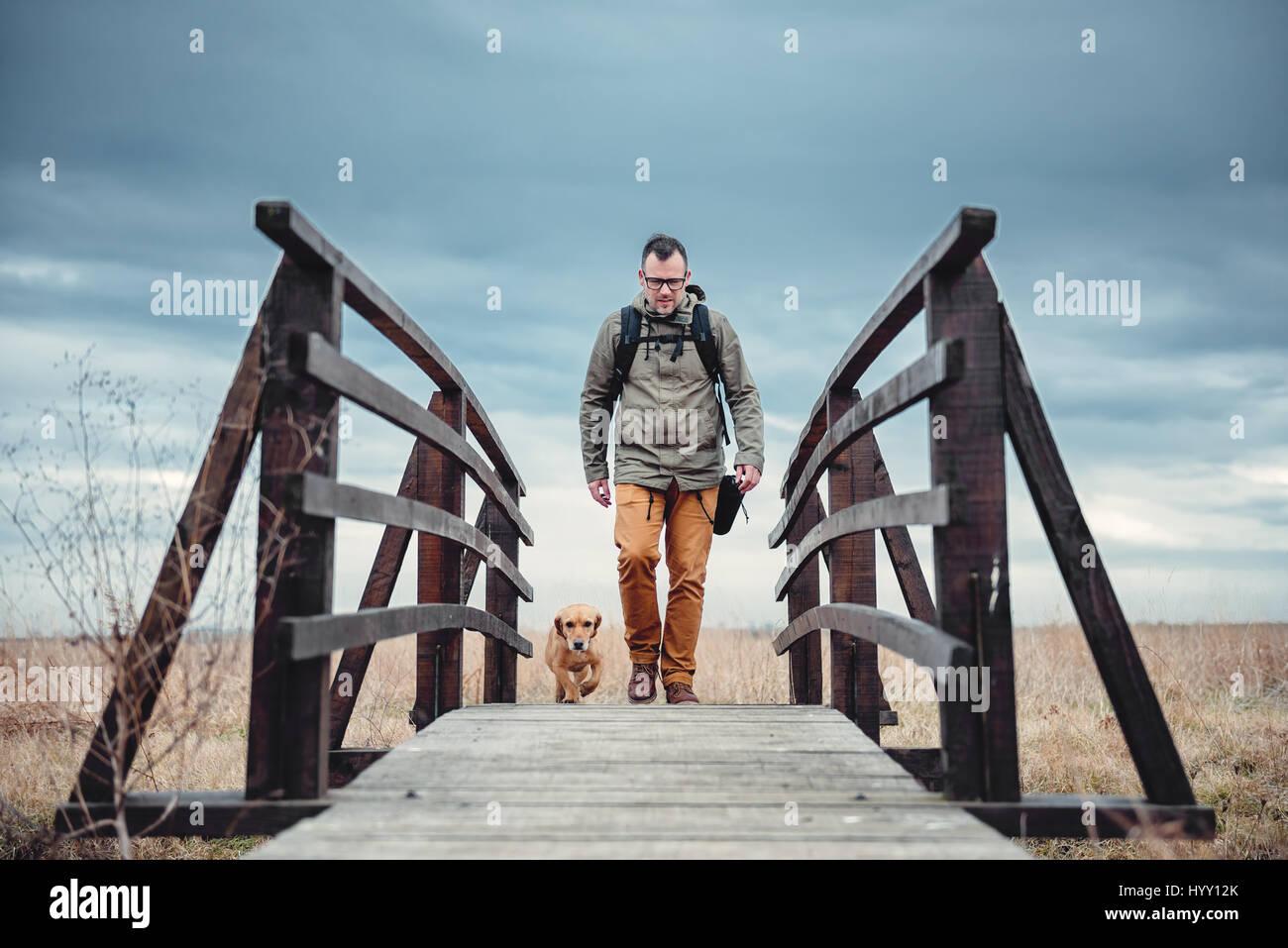 Caminante y perro cruzar el puente de madera sobre el día nublado Imagen De Stock