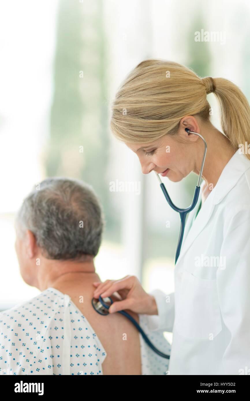 Doctora con estetoscopio en paciente masculino. Imagen De Stock