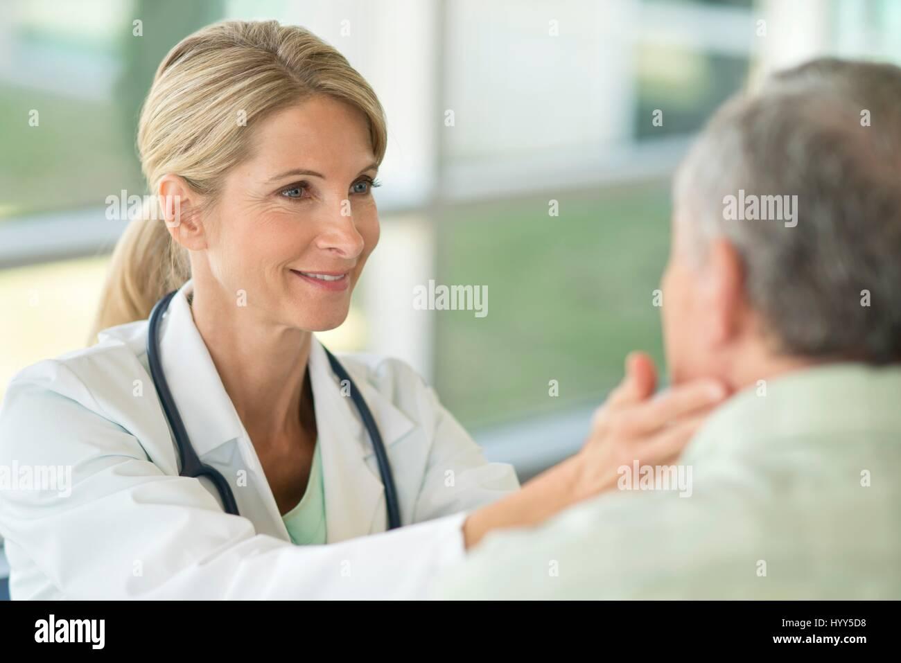 Doctora tocando el hombre superior del cuello. Imagen De Stock