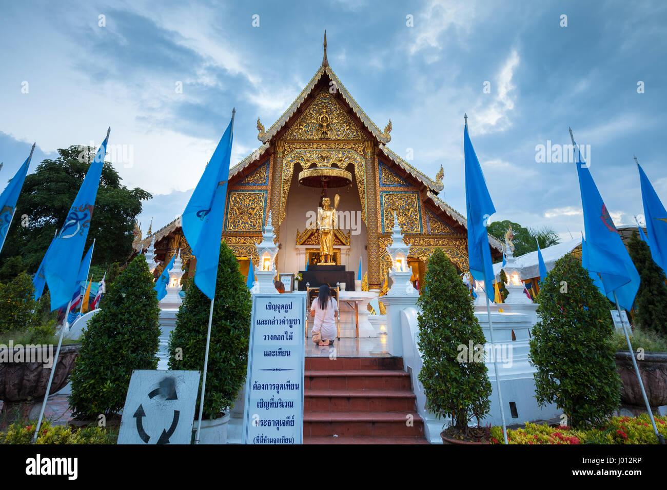 Chiang Mai, Tailandia - Agosto 21, 2016: la mujer de orar en el templo Wat Phra Singh decorado con banderas azules de Queens el 21 de agosto de 2016 en Chinag Mai, Tha Foto de stock