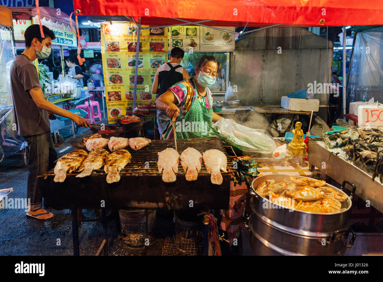 Chiang Mai, Tailandia, 27 de agosto de 2016: La mujer cocina tailandesa parrilladas de pescado en el mercado del Imagen De Stock