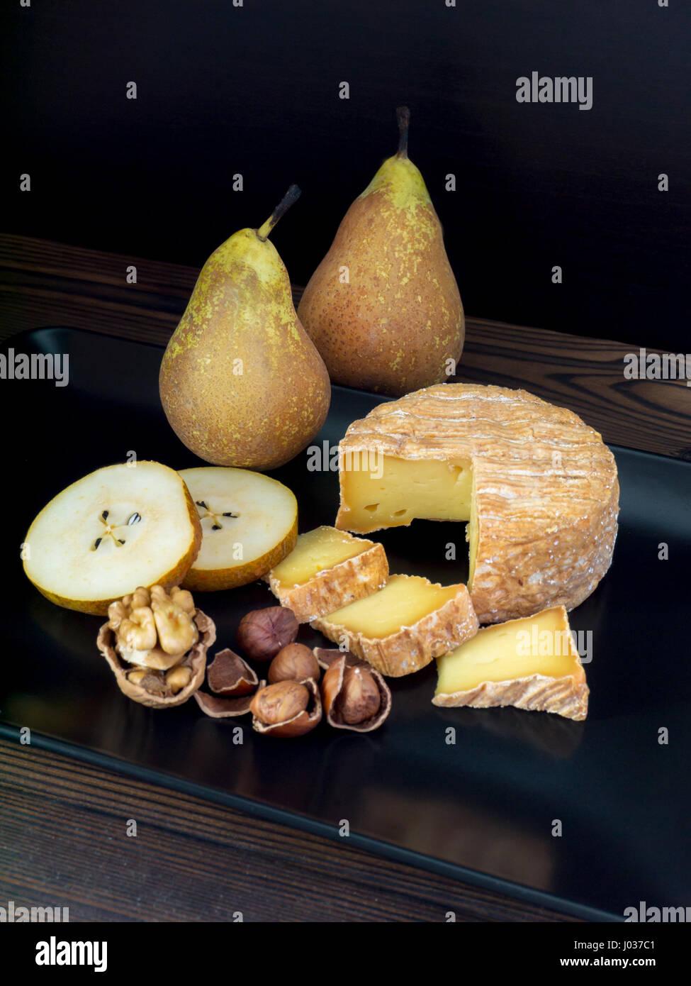 Corteza lavada suave queso, nueces, avellanas y las peras en la placa negra Imagen De Stock