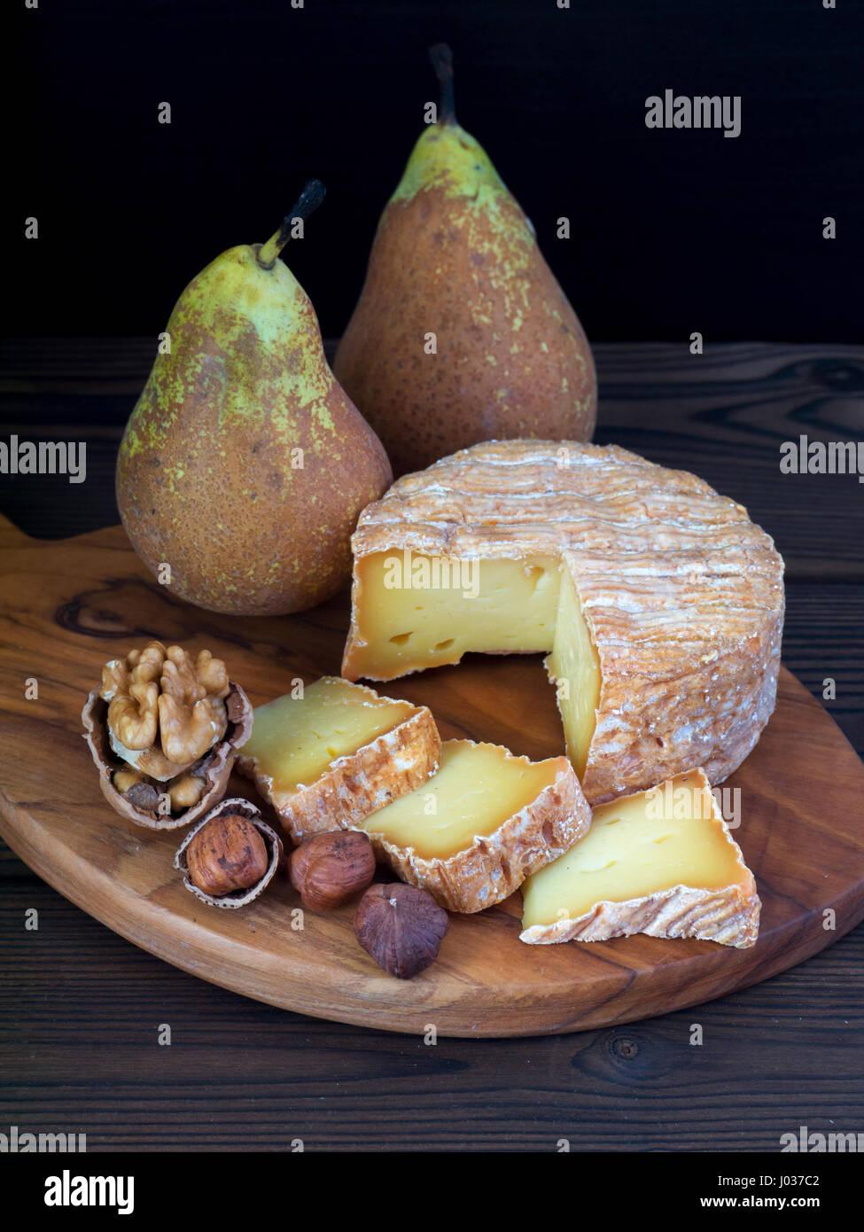 Corteza lavada suave queso, nueces, avellanas y las peras en la placa de madera Imagen De Stock