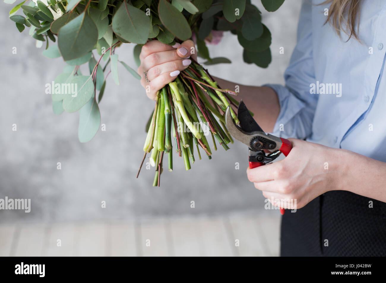 Floristería en el trabajo: bastante joven haciendo moda moderno ramo de flores diferentes Imagen De Stock