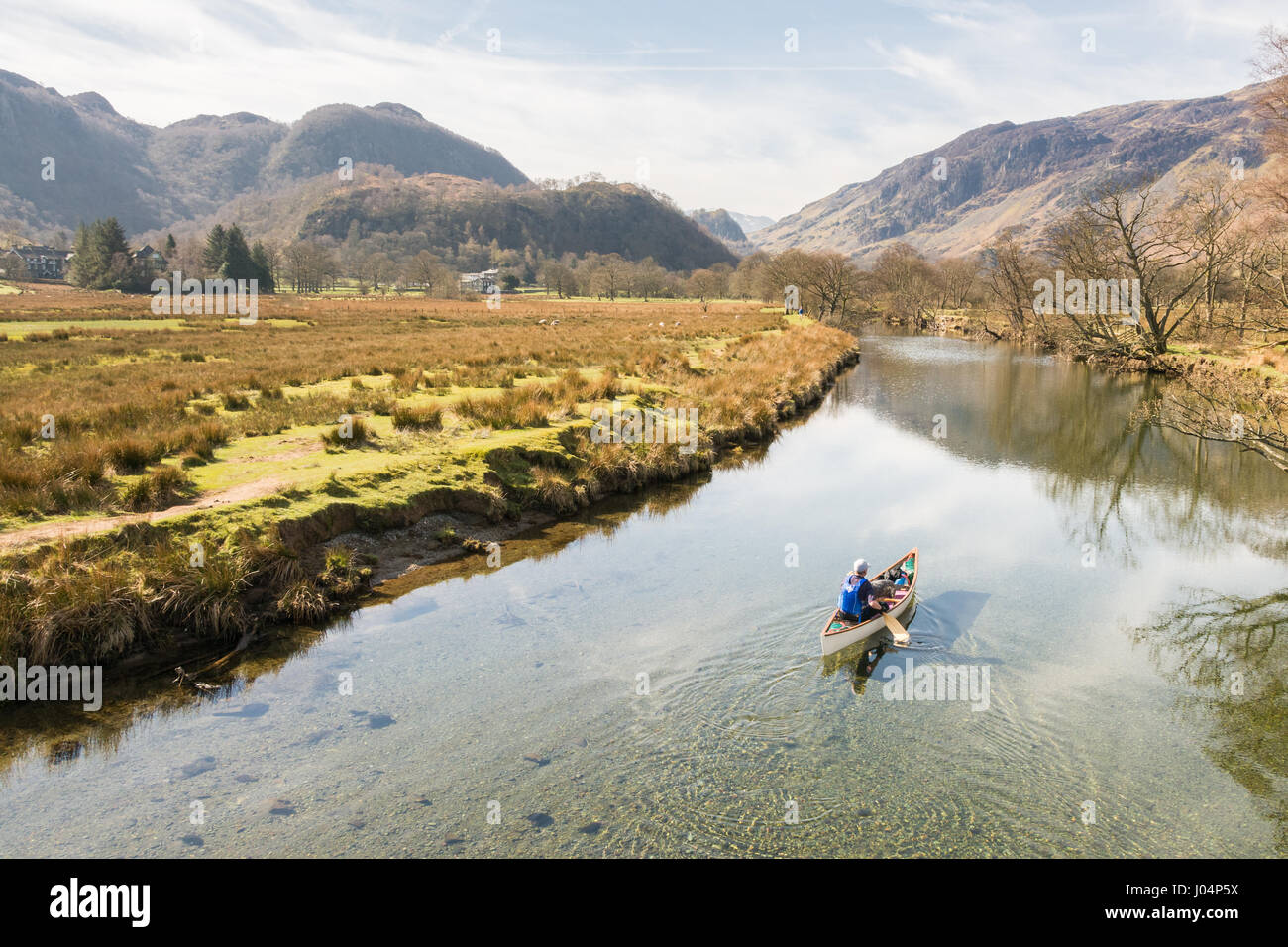 Piragüismo canoa en el Lake District, Inglaterra, Reino Unido - un hombre y su perro conoeing en el río Imagen De Stock