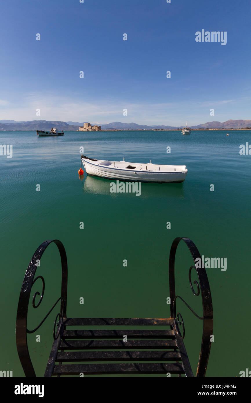 Pier Pasos, tradicionales barcos pesqueros y en la Fortaleza de Bourtzi distante fondo en Nafplion, Grecia- Foto Imagen De Stock
