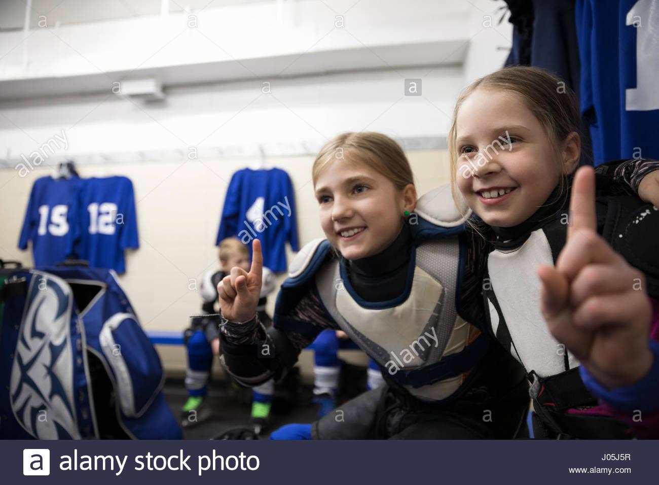 Seguro girl jugadores de hockey sobre hielo gesticulando número 1 en el vestuario Imagen De Stock