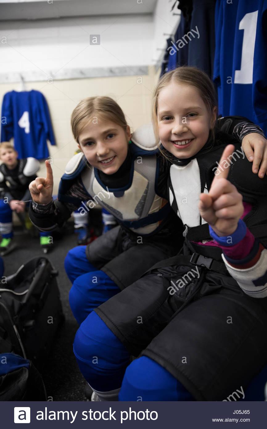 Retrato seguro girl jugadores de hockey sobre hielo gesticulando número 1 en el vestuario Imagen De Stock