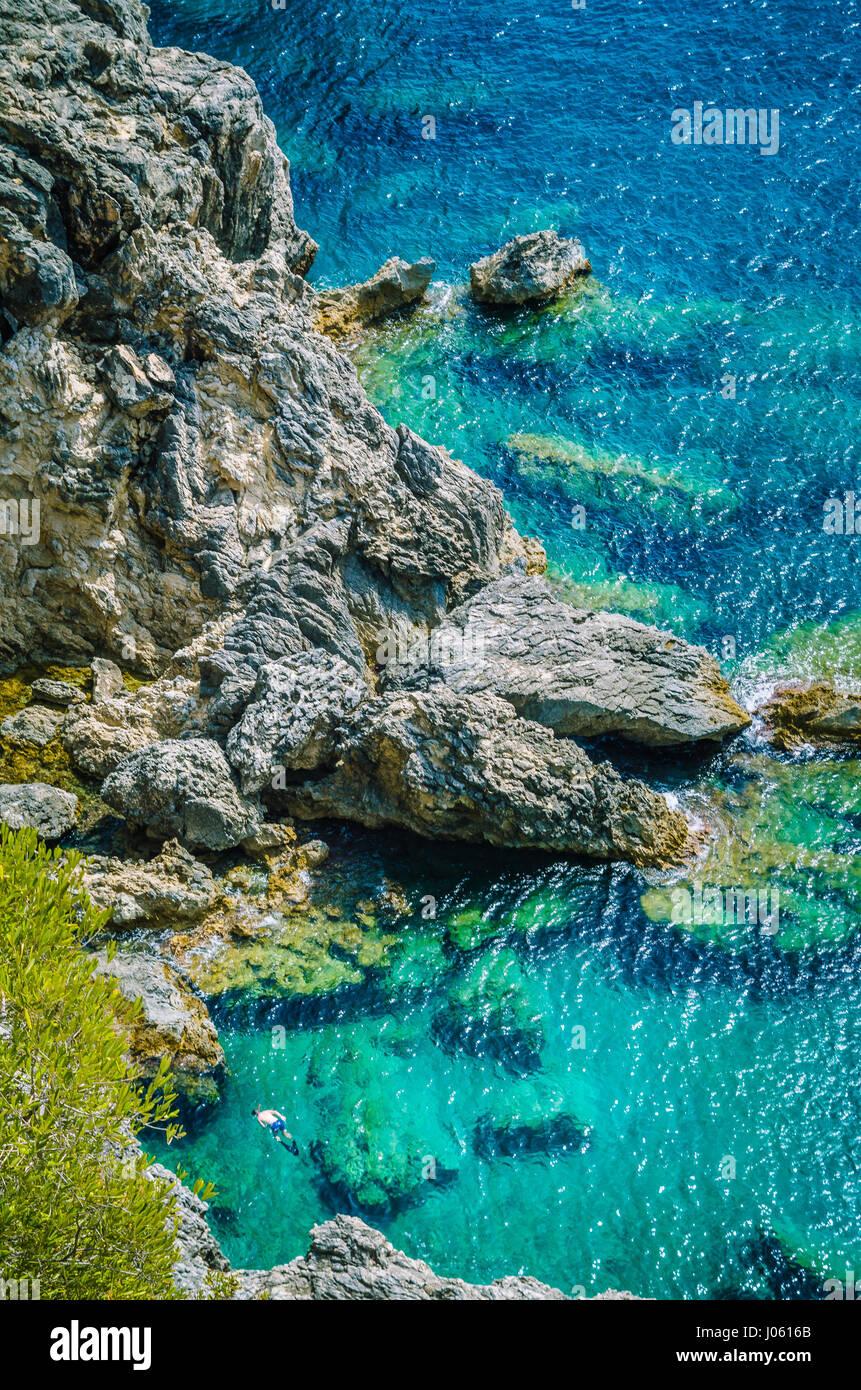 Los turistas shorkling entre rocas en la bahía azul de Paleokastritsa hermosa isla de Corfú, Grecia Imagen De Stock