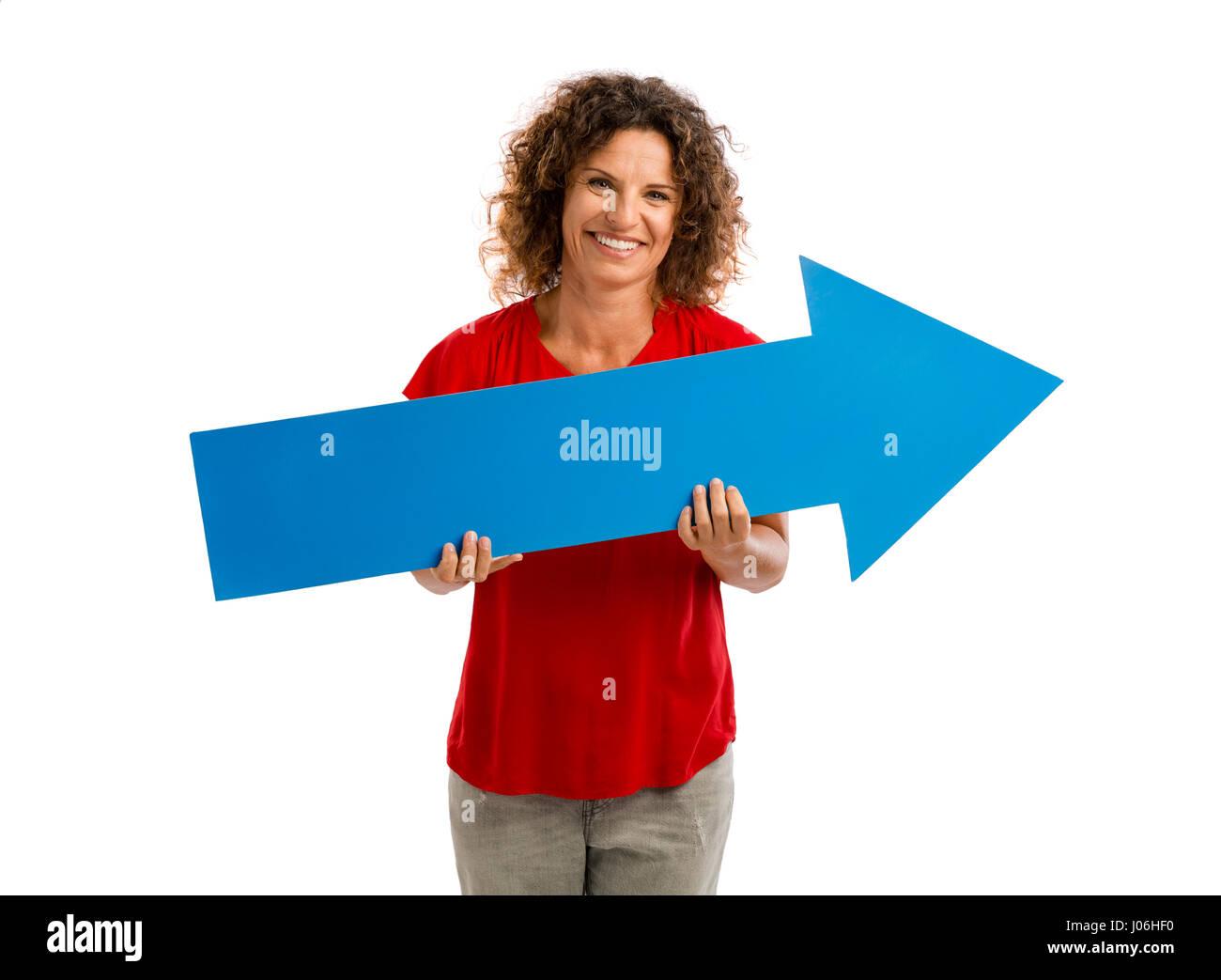 Feliz mujer madura sosteniendo una flecha azul Imagen De Stock