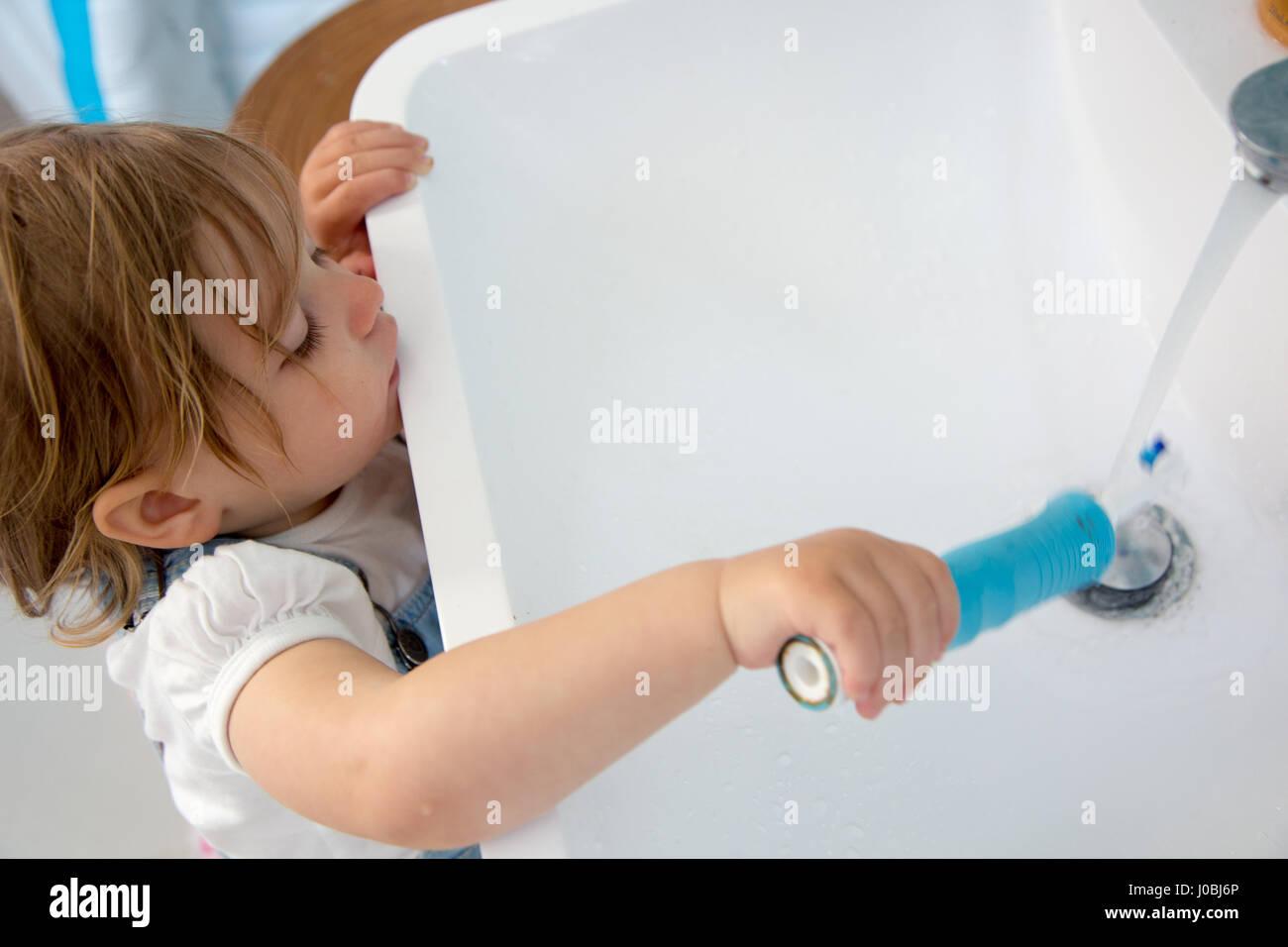 Niña Niño cepillarse los dientes con un cepillo de dientes eléctrico de  adultos. c4c5f464ebe9