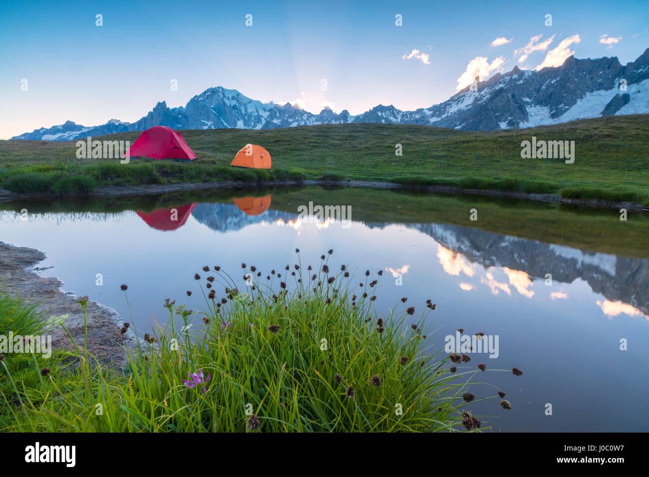 Tiendas de campaña en las verdes praderas rodeadas de flores y lago alpino, el Mont De La Saxe, Courmayeur, Imagen De Stock