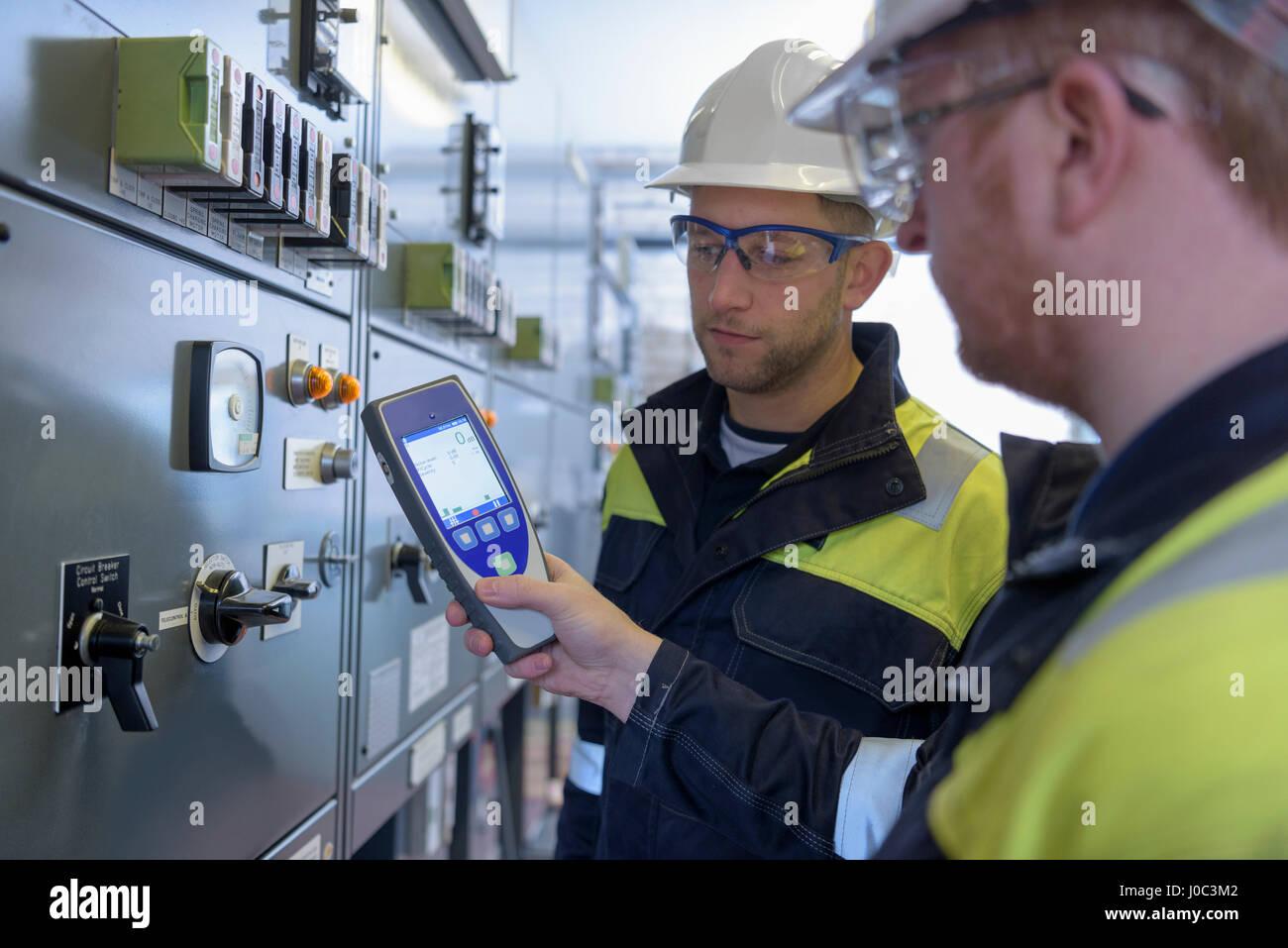 Los trabajadores para comprobar el ruido en la subestación eléctrica Imagen De Stock