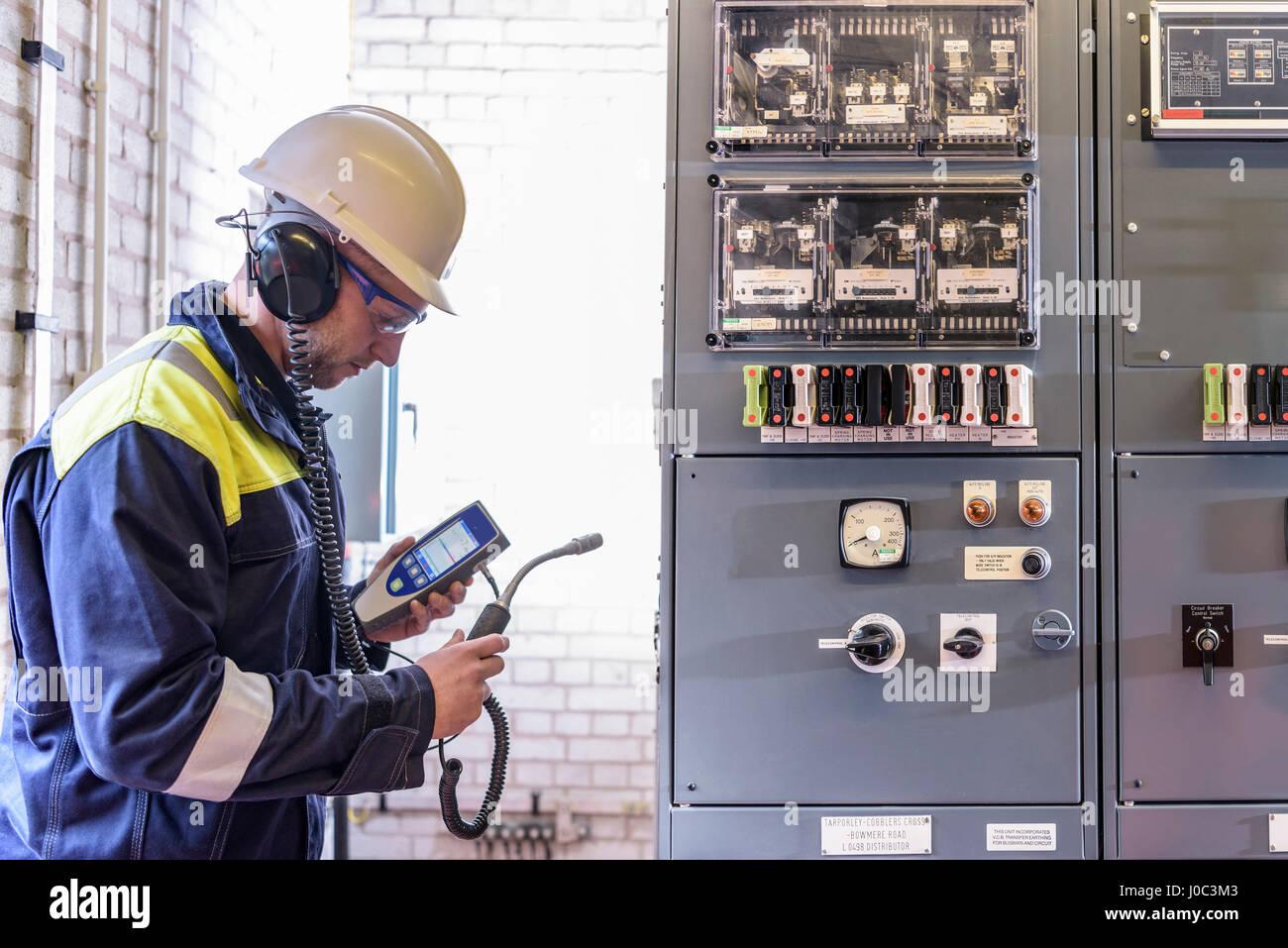 Trabajador para comprobar el ruido en la subestación eléctrica Imagen De Stock