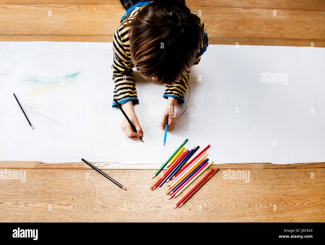 Vista aérea del niño acostado en el suelo el dibujo sobre papel largo Imagen De Stock