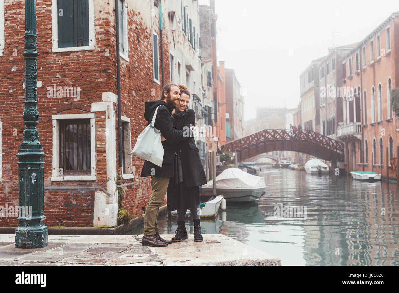 Par abrazar a Misty canal Waterfront, Venecia, Italia Imagen De Stock