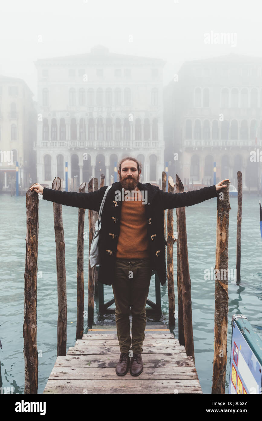 Retrato de un hombre adulto medio sobre Misty canal pier, Venecia, Italia Imagen De Stock