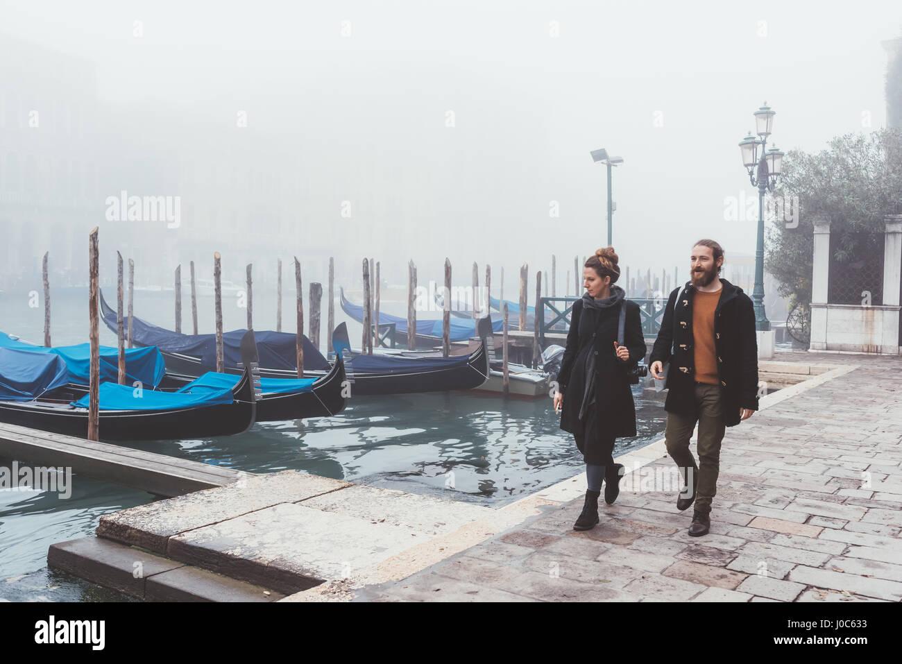 Pareja paseando por misty canal Waterfront, Venecia, Italia Imagen De Stock