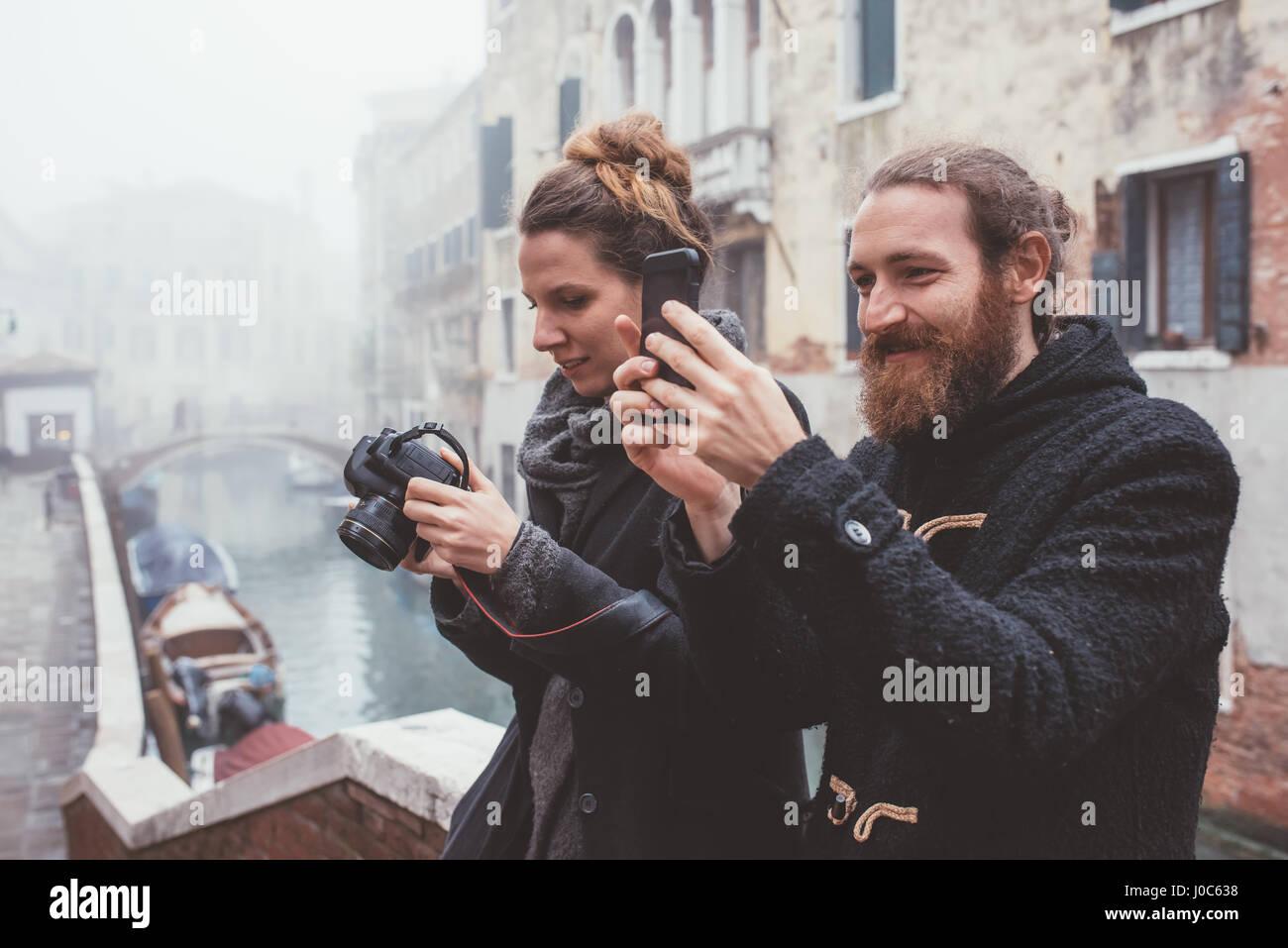 Par fotografiar sobre Misty canal Waterfront, Venecia, Italia Imagen De Stock
