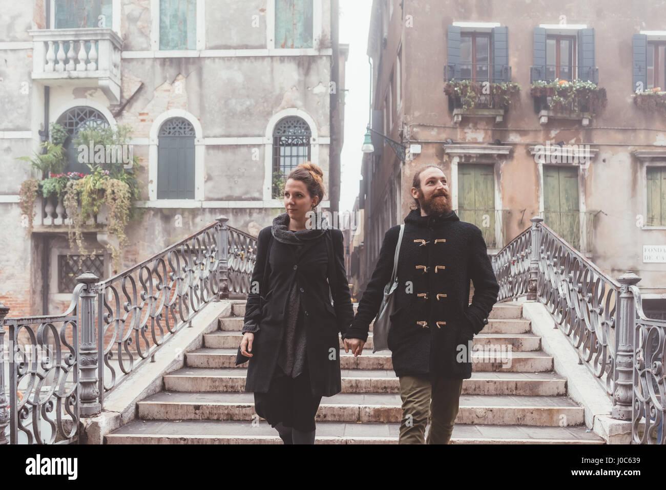 Par la celebración de manos y bajando las escaleras, Venecia, Italia Imagen De Stock