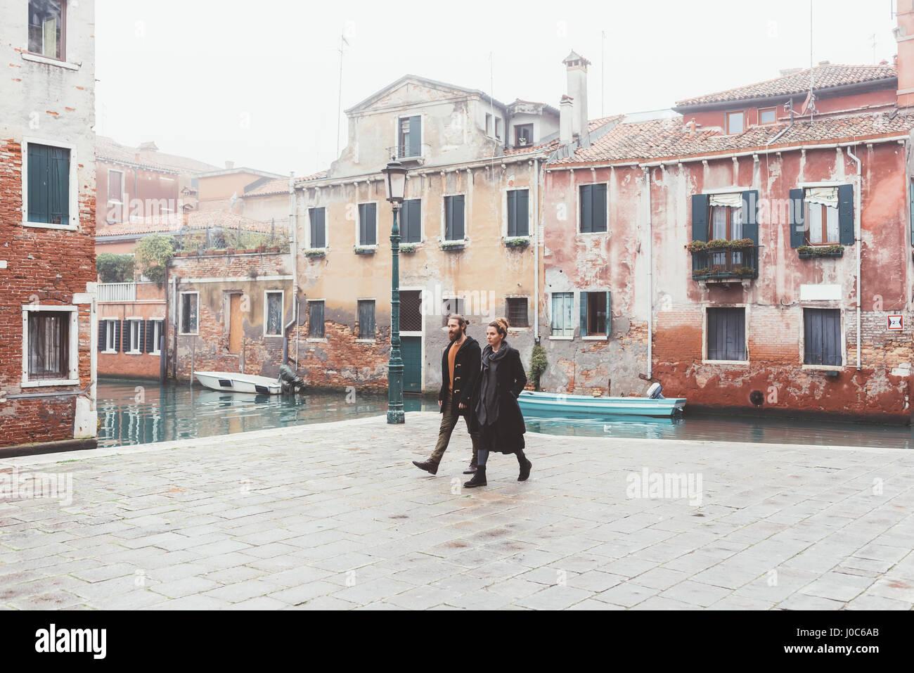 Pareja paseando por la orilla del canal, Venecia, Italia Imagen De Stock