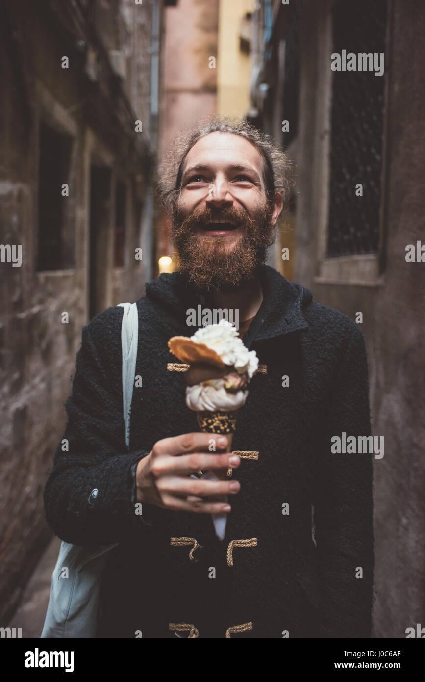 Mitad hombre adulto con helado en el oscuro callejón, Venecia, Italia Imagen De Stock