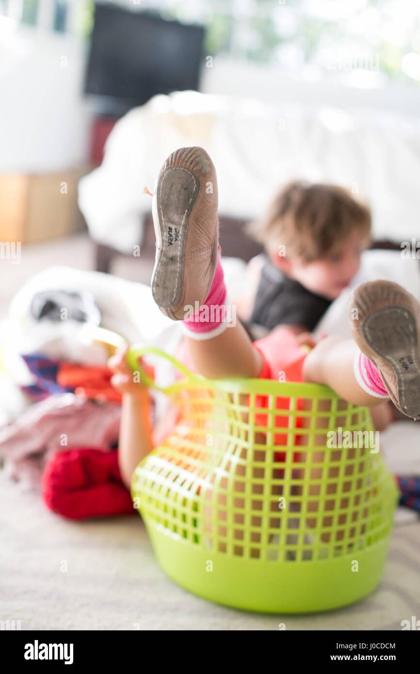 Las niñas las piernas que sobresalen de la canasta de lavandería Imagen De Stock
