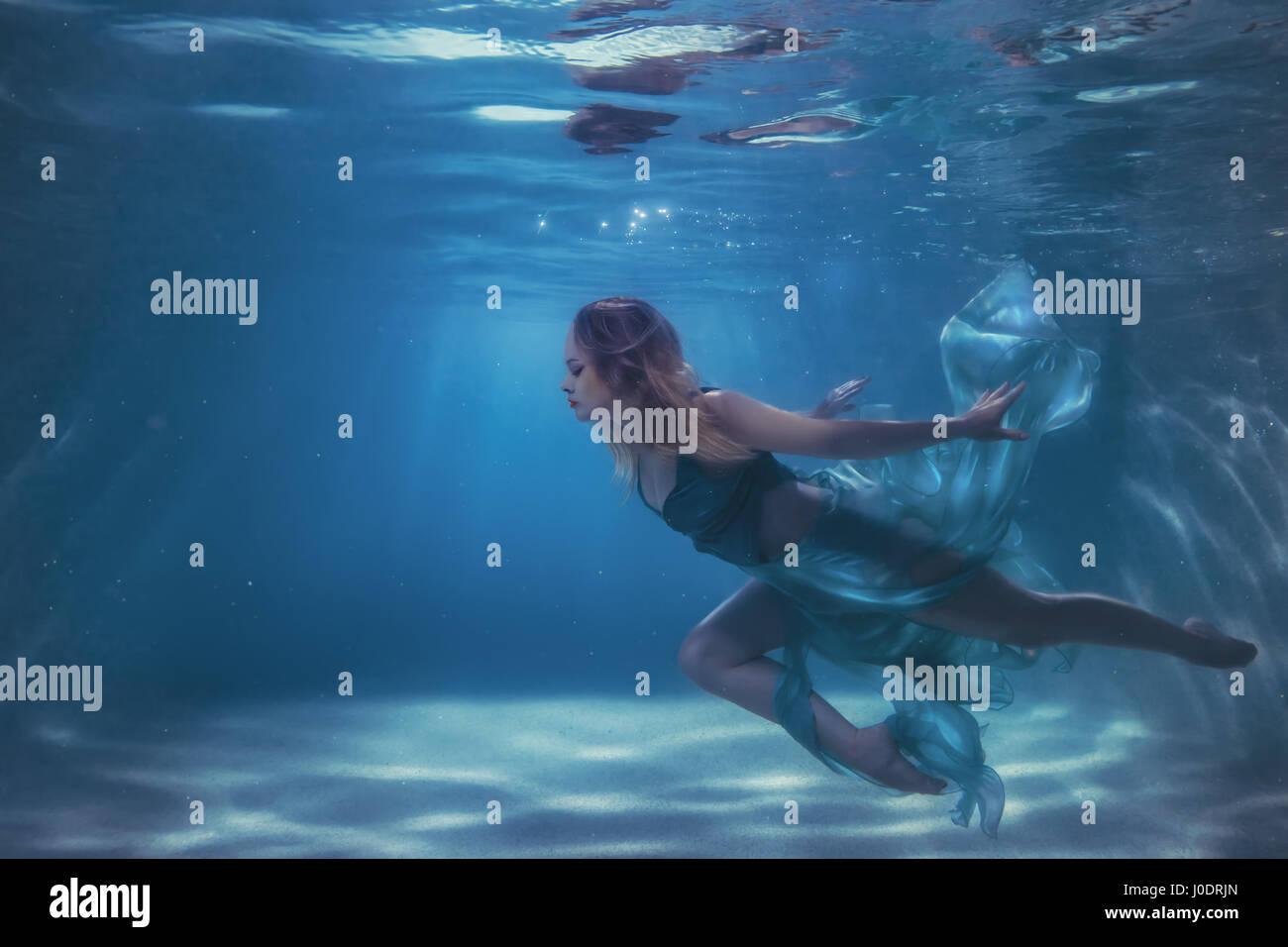 Mujer en un vestido se sumerge en el agua, desarrolla tejido subwater. Foto de stock