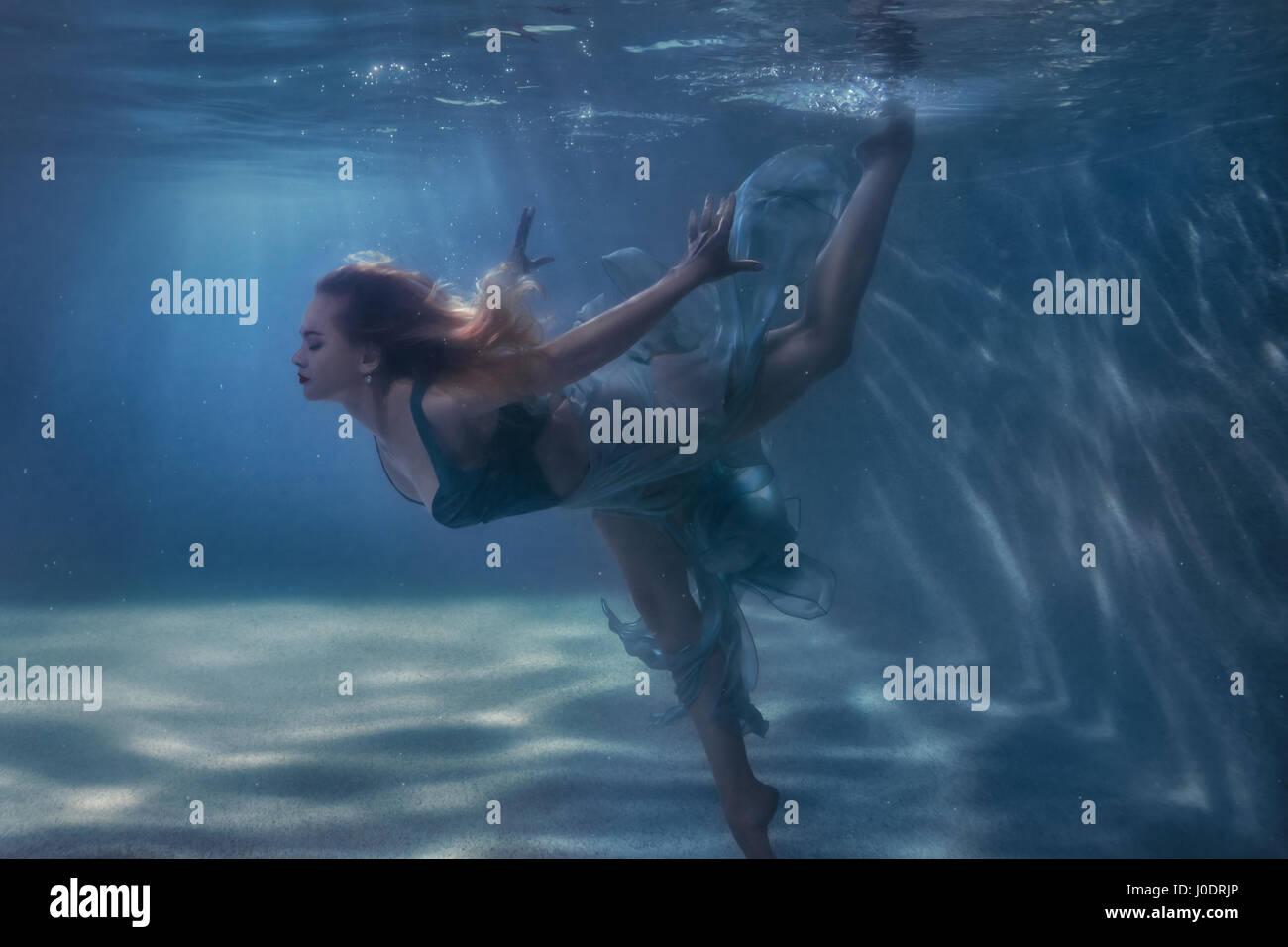 Mujer en un vestido es baile submarino. Foto de stock