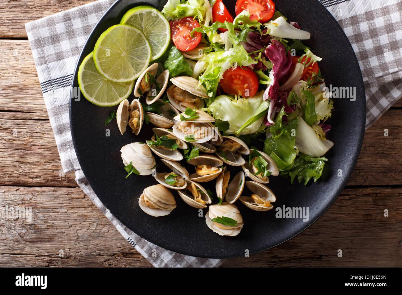 Delicatessen las almejas con limón y ensalada de verduras frescas de cerca en una placa. Vista desde arriba Imagen De Stock