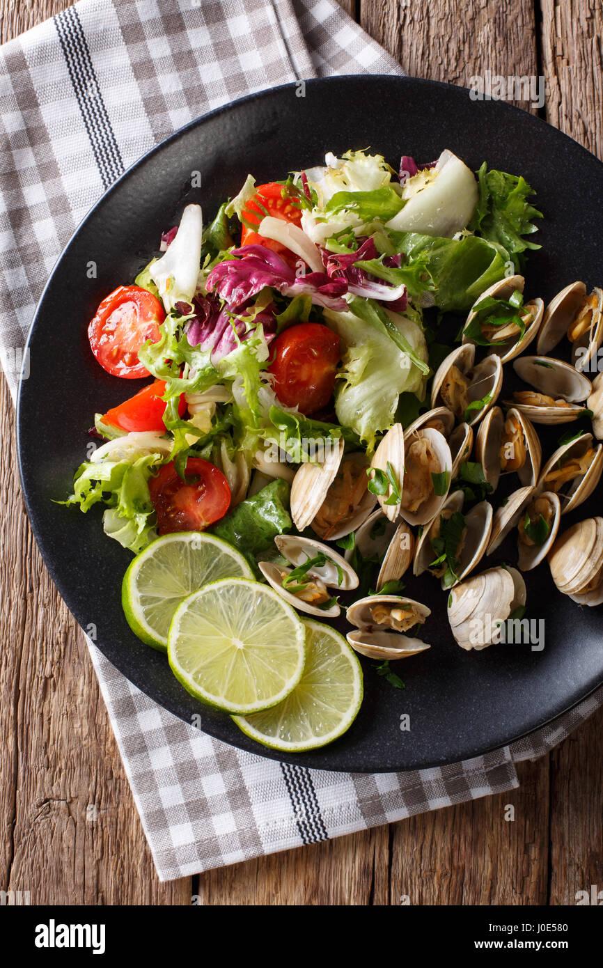 Delicatessen las almejas con limón y ensalada de verduras frescas de cerca en una placa. Vista vertical desde Imagen De Stock