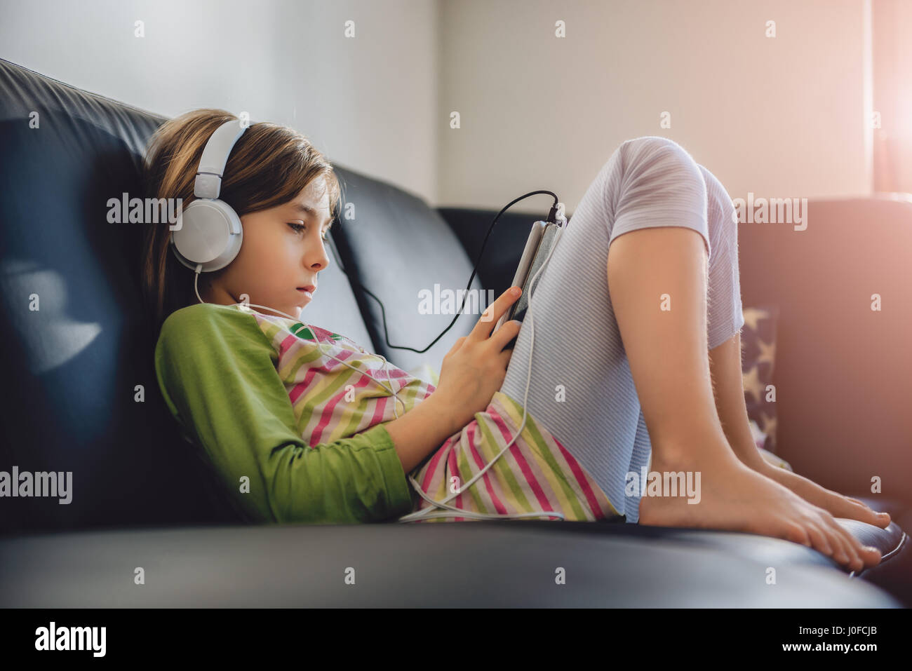 Chica sentada en un sofá negro con tablet y escuchar música Imagen De Stock
