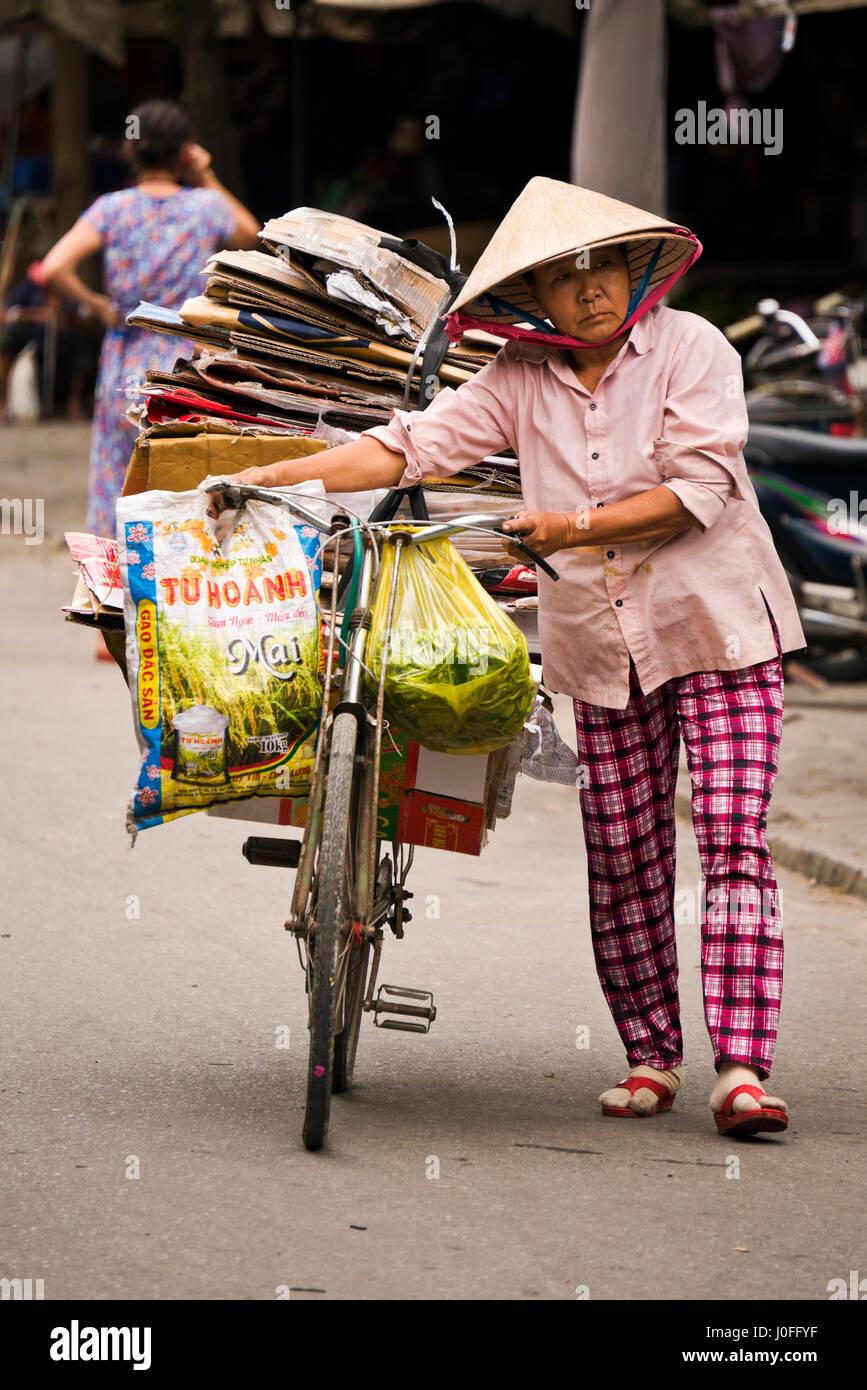 Vertical de una anciana empujando una bicicleta cargada con cajas de cartón  por las calles de 556d0bc5e0d