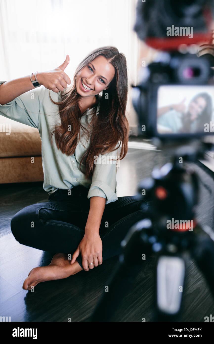 Los jóvenes vlogger mostrando pulgar arriba firmar grabando su videoblog. Mujer sonriente sentado en el suelo Imagen De Stock