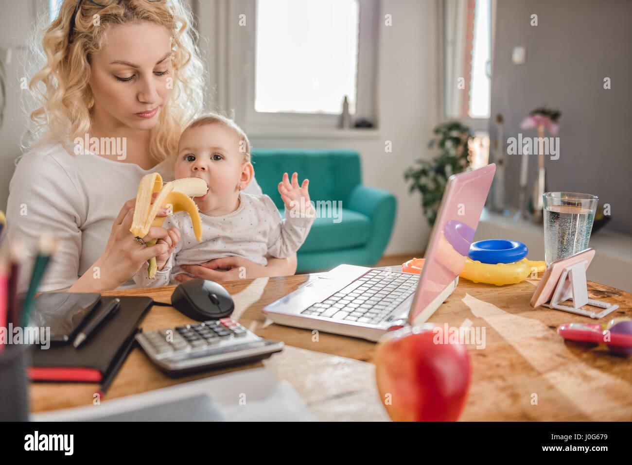 Madre alimentando al bebé en su oficina doméstica con plátano Imagen De Stock