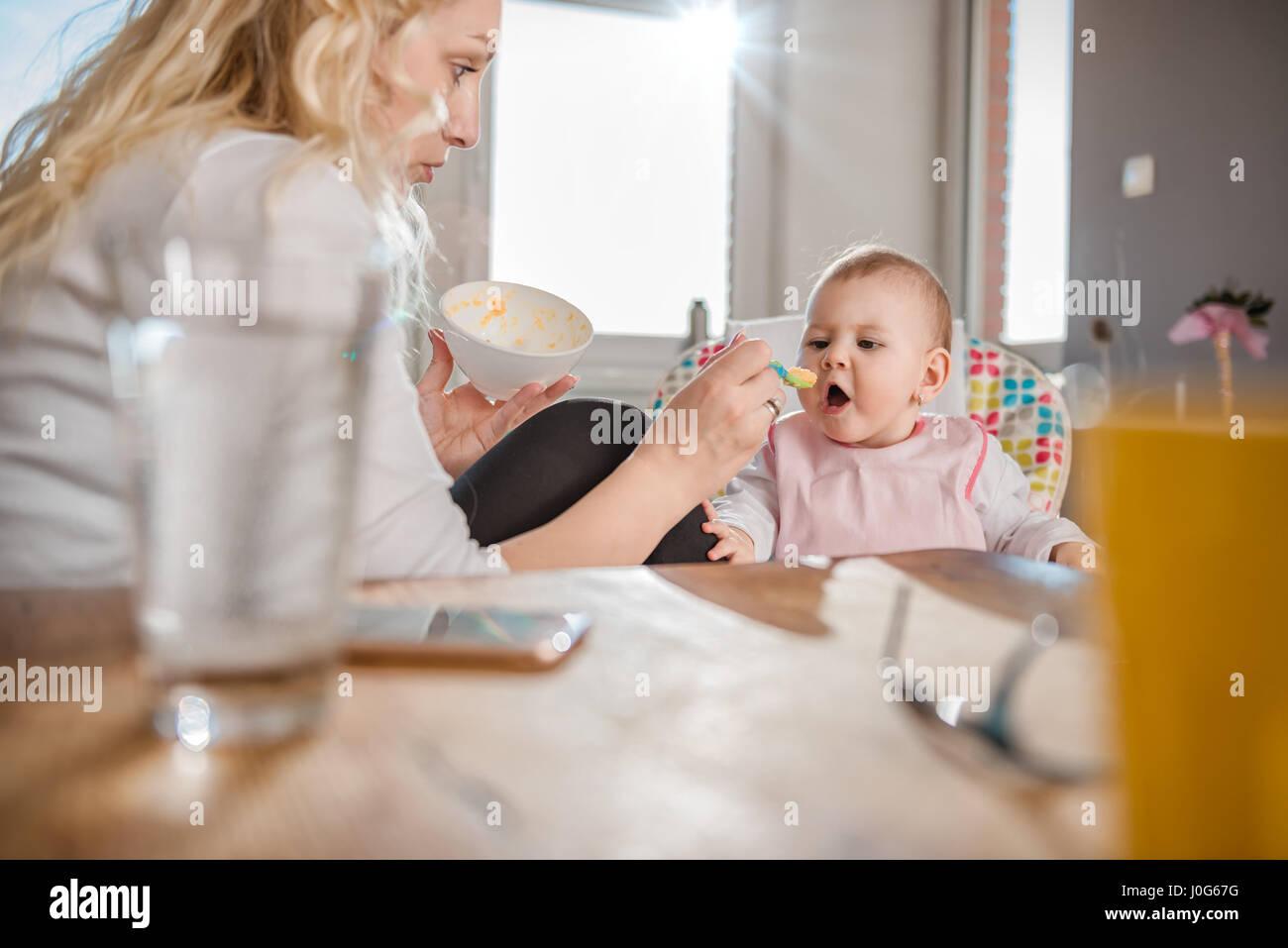 Madre alimentando a bebé en el hogar Imagen De Stock