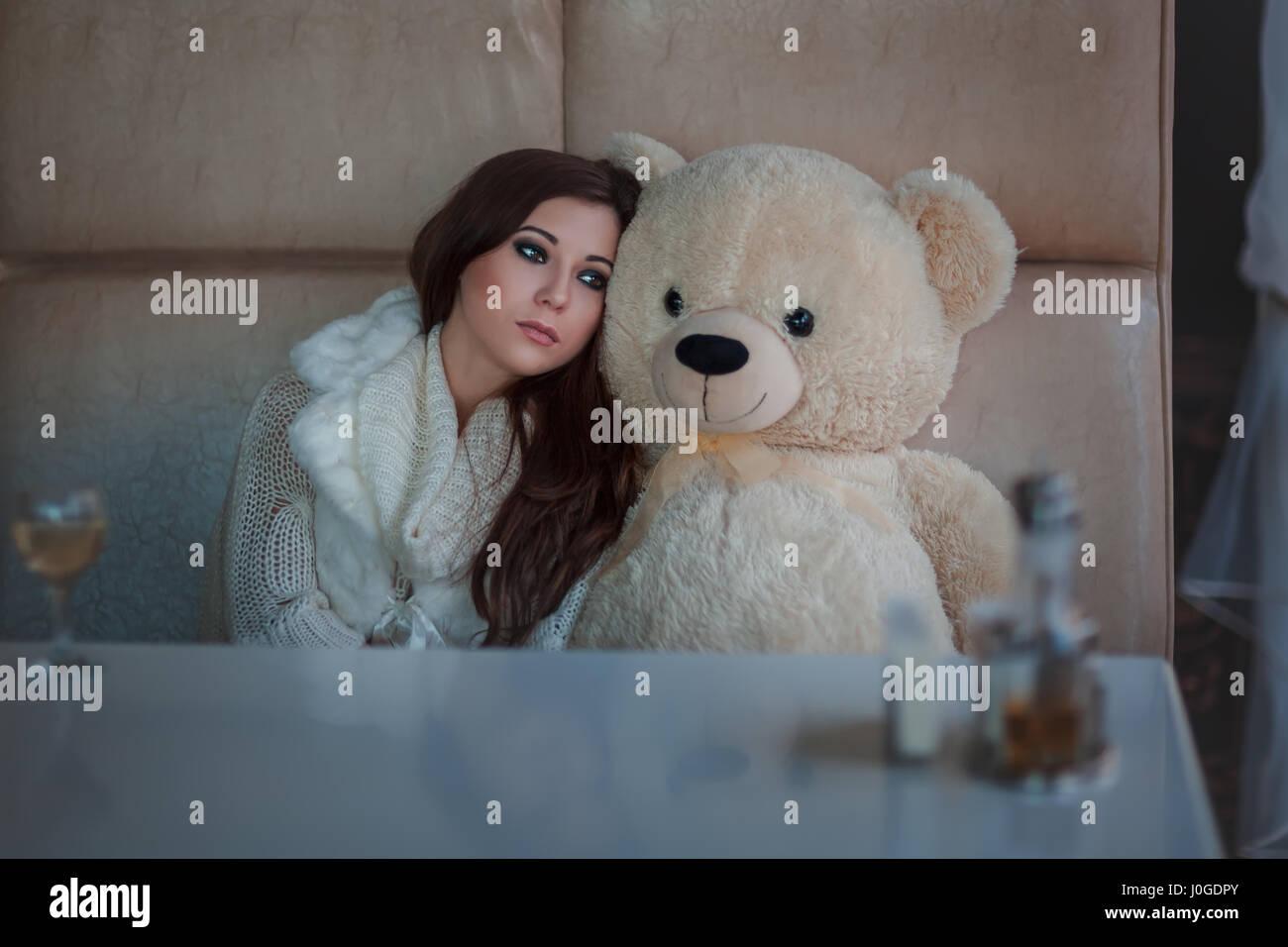 Triste chica con el oso de juguete sentado a la mesa. Imagen De Stock