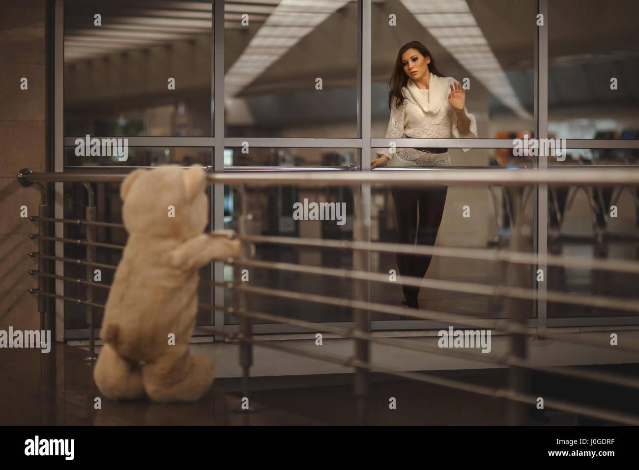 Niña triste saludando con la mano, ella dice adiós con un oso de peluche y es muy triste. Imagen De Stock